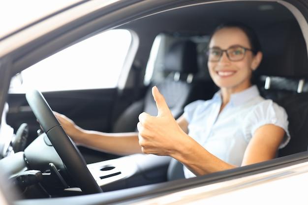 자동차 바퀴 뒤에 앉아 신용 개념으로 자동차를 구매하는 근접 촬영을 엄지손가락으로 보여주는 여성