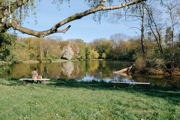 Woman sitting on a bench by the pond in a beautiful spring park