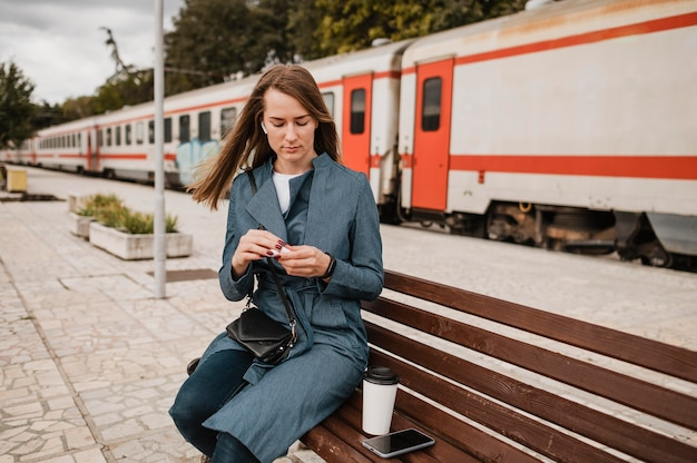 Woman sitting on bench next to her coffee
