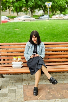 Woman sitting on the bench in the park with take away food and coffee, having lunch break from work