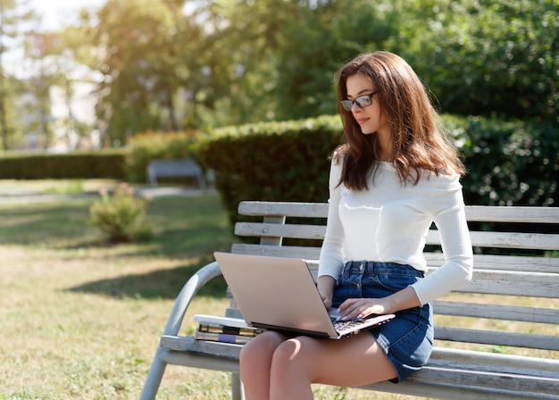 Woman sitting on a bench in the park and working on a laptop