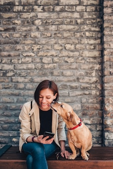 Woman sitting on the bench and using phone while dog is licking her face