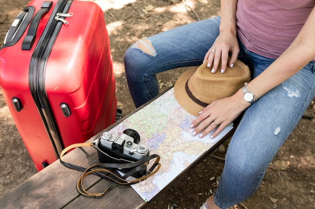 Woman sitting on a bench with travelling accessories