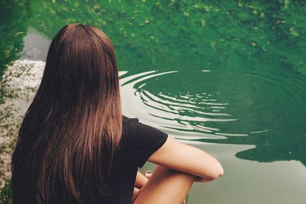 Женщина, сидящая у водоема