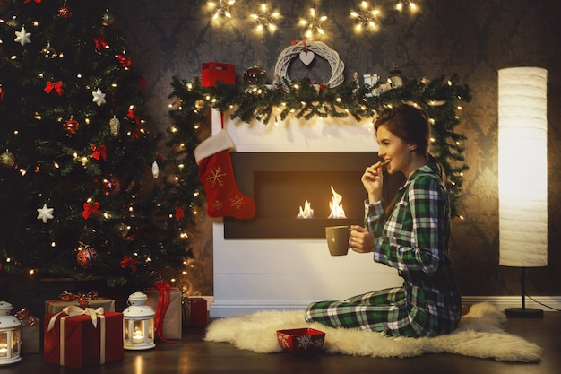 Woman sitting beside fireplace is drinking hot tea with cookies