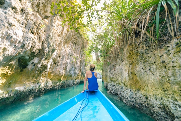 Woman sitting on boat in narrow canyon and turquoise lagoon at bair island