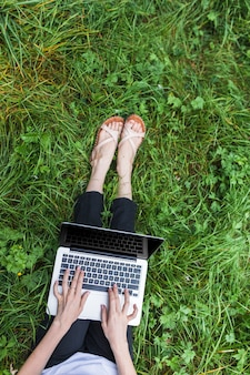 Woman sitting on bright grass with laptop
