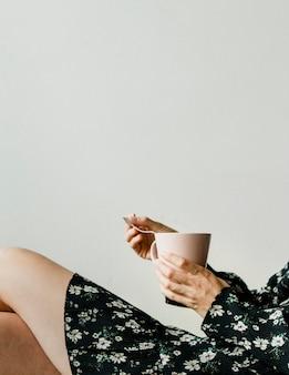 お茶と白い壁のそばに座っている女性