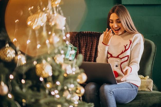 Donna che si siede dall'albero di natale e dalle vendite online di compera