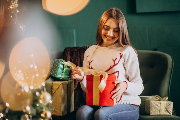 Woman sitting by christmas tree and unpacking christmas present
