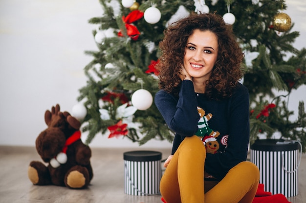 Woman sitting by christmas tree
