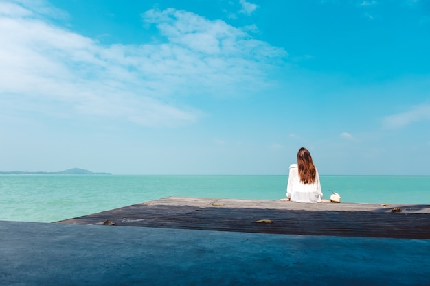 Woman sitting by the sea Premium Photo