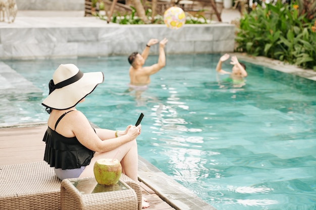 Woman sitting by swimming pool ans checking social media via smartphone when her husbad and son playing with inflatable ball in background