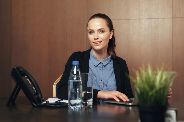 Woman sitting by the table with laptop in office