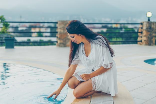 プールのそばに座って、昼間に家で夜のドレスの水に触れる女性