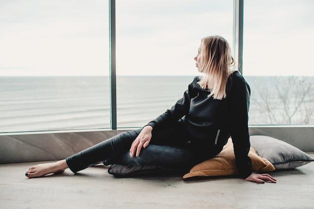 アパートの窓際に座っている女性