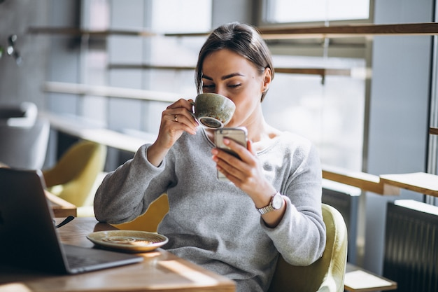 Woman sitting in a cafe drinking coffee and working on a computer