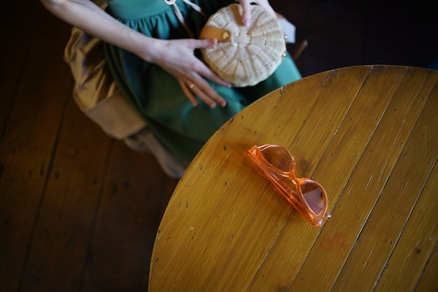 Woman sitting in a cafe glasses on the table rest