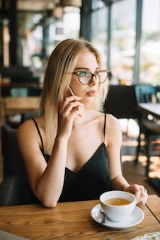 Woman sitting in cafe talking on mobile phone looking away