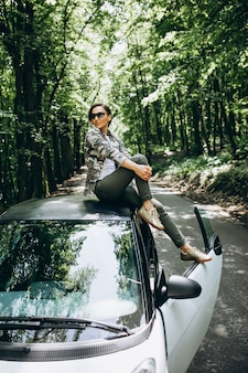 Woman sitting on car roof in the forest