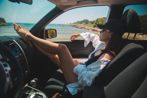 Woman sitting in car show sexy legs looking at summer sea beach vacation