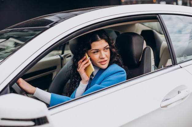 Woman sitting in car and using mobile phone