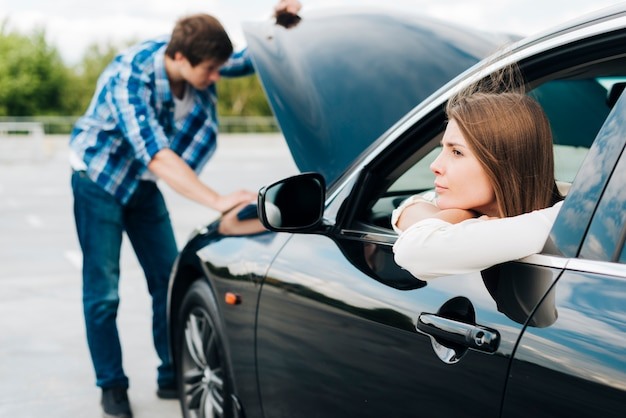 Woman sitting in car while man checks engine