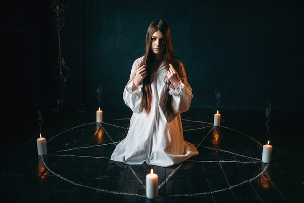 Woman sitting in the center of pentagram circle