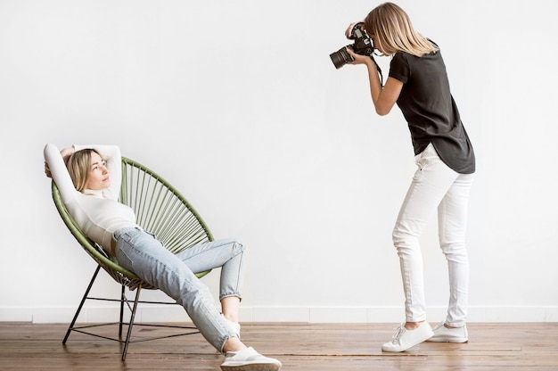 Woman sitting on a chair and photographer