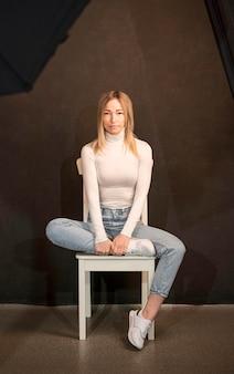 Donna che si siede su una sedia e su una posa