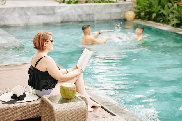 Woman sitting on chaise-lounge and reading book when her husband and son playing with inflatable ball in swimming pool