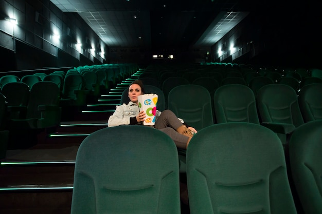 Woman sitting in cinemahall with popcorn