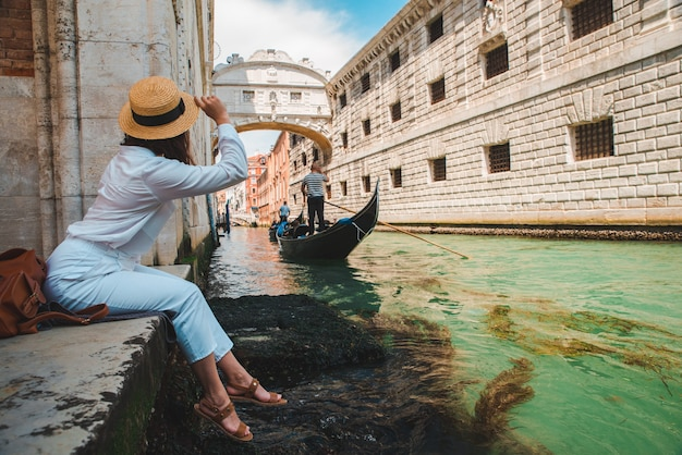 Woman sitting at city quay at venice italy enjoying the view of canals with gondolas copy space