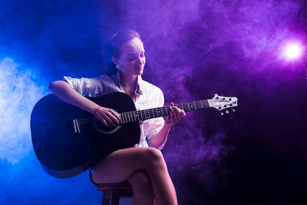 Woman sitting in the classical position for playing the guitar