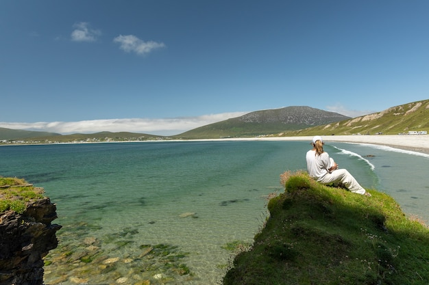 Woman sitting on cliff looking at keel beach in achill island ireland