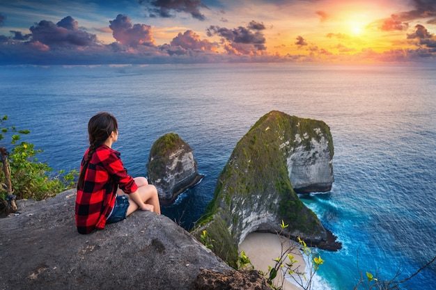 Woman sitting on cliff and looking at sunset at kelingking beach in nusa penida island, bali, indonesia.