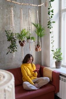 Woman sitting on couch under cotton macrame plant hanger with houseplants, using mobile phone