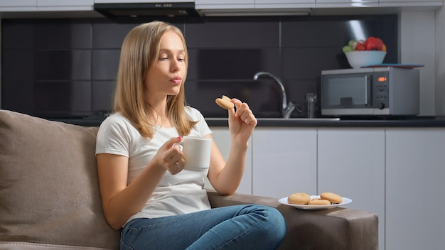 Woman sitting on couch and eating tasty cookies with cup of tea.