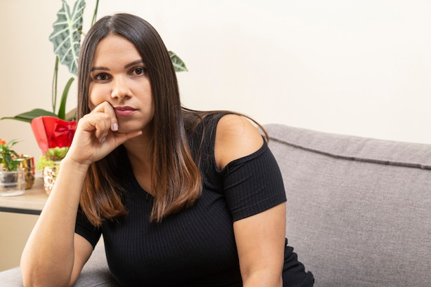 Woman sitting on the couch, hand on chin, thoughtful.