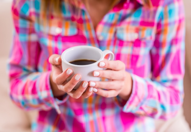 Woman sitting on the couch at home and drink tea or coffee