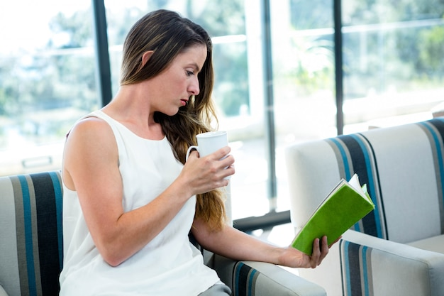 Woman, sitting on a couch, reading a book and drinking a coffee