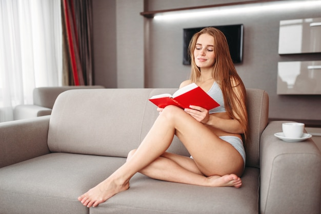 Woman sitting on the couch and reads the book
