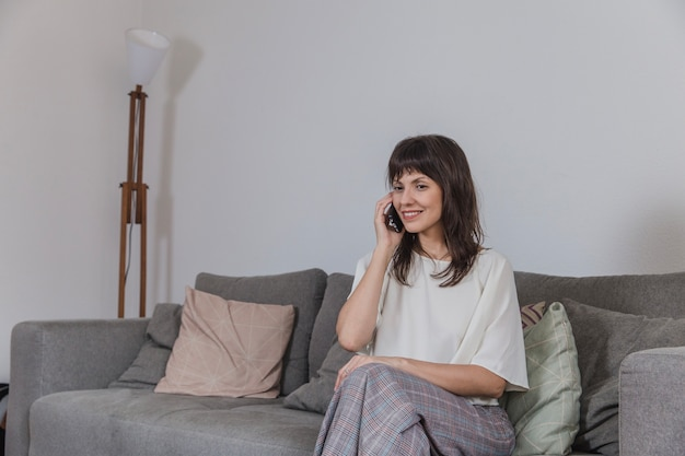 Woman sitting on couch and talking on the phone