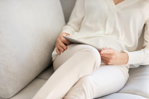 Donna seduta sul divano e utilizzando tablet