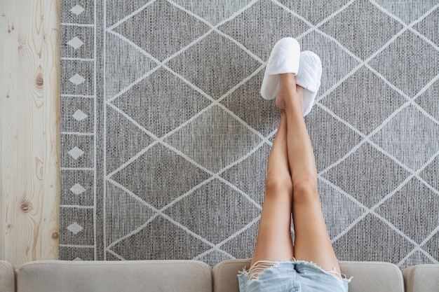 Woman sitting on the couch with her feet on the carpet