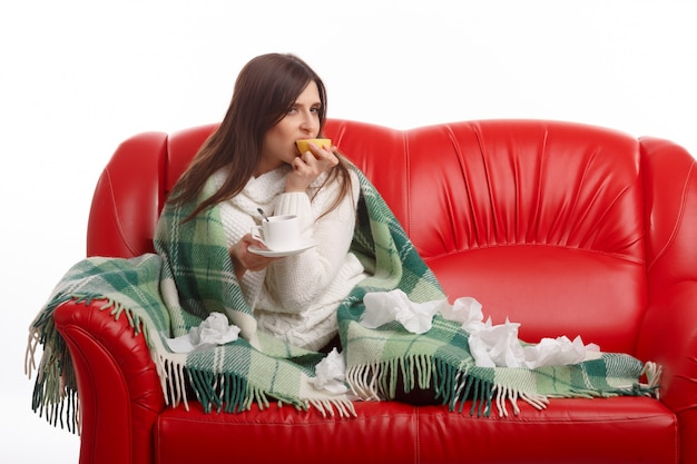 Woman sitting on the couch with a lemon in the mouth