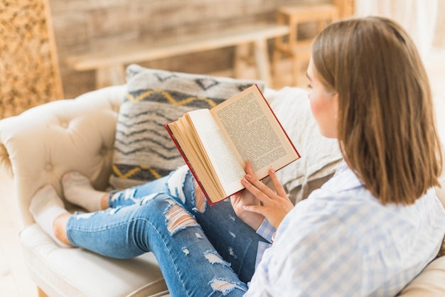 Woman sitting on couch with reading book