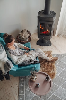 Woman sitting in a cozy armchair with a warm blanket using a m
