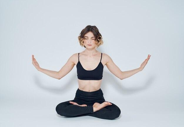 床に足を組んで座って、手で身振りで示す女性瞑想ヨガアーサナ