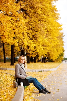 Woman sitting on a curb with notebook in autumn park with golden trees